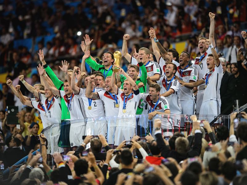 Philipp Lahm of Germany lifts the World Cup trophy with teammates after defeating Argentina 1-0 in extra time during the 2014 FIFA World Cup Brazil Final match between Germany and Argentina at Maracana on July 13, 2014 in Rio de Janeiro, Brazil. (Photo by Matthias Hangst/Getty Images)
