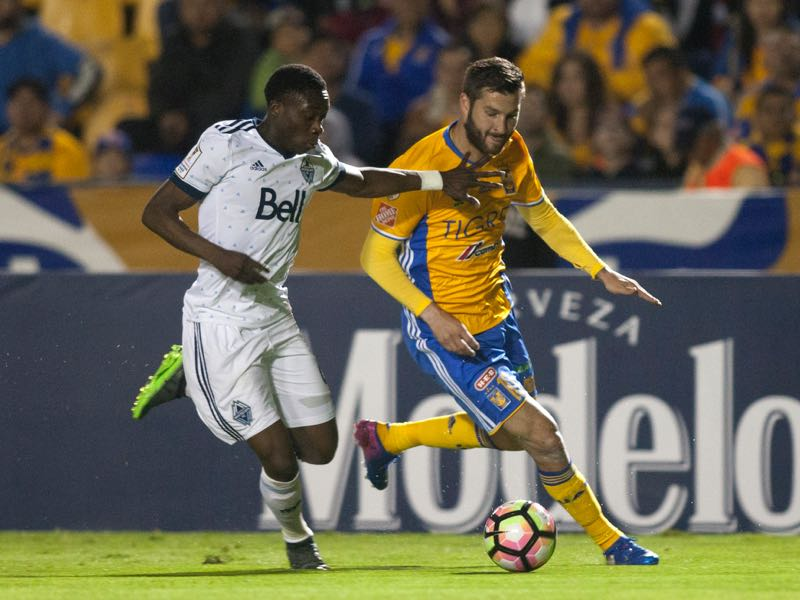 Alphonso Davies (l.) fights off Tigres star Gignac in a crucial Whitecaps Concacaf Champions League fixture (JULIO CESAR AGUILAR/AFP/Getty Images)