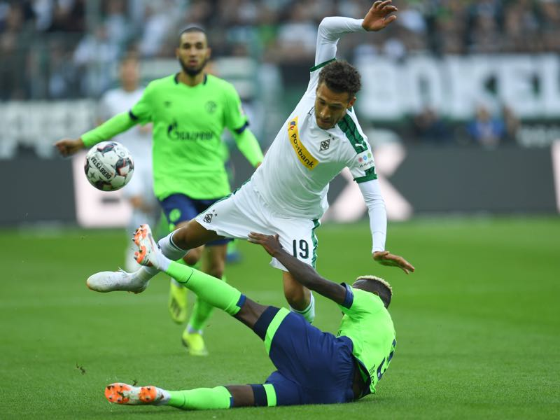 Borussia Mönchengladbach vs Schalke - US midfielder Fabian Johnson and Schalke's Moroccan defender Hamza Mendyl (bottom) fall down during the German First division Bundesliga football match between Monchengladbach and Shalke 04 on September 15, 2018 in Monchengladbach. (Photo by Patrik STOLLARZ / AFP)