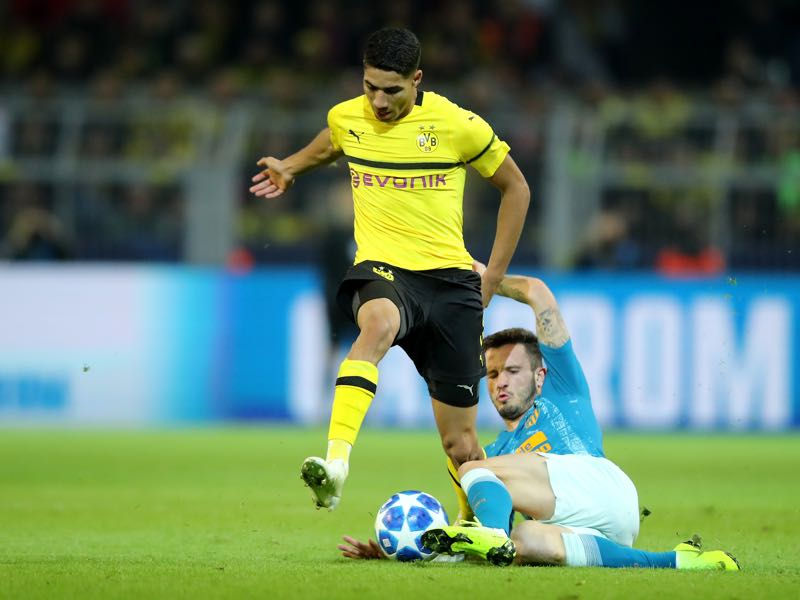 Borussia Dortmund v Atletico Madrid - Achraf Hakimi of Borussia Dortmund is challanged by Saul Niguez of Atletico Madrid during the Group A match of the UEFA Champions League between Borussia Dortmund and Club Atletico de Madrid at Signal Iduna Park on October 24, 2018 in Dortmund, Germany. (Photo by Christof Koepsel/Bongarts/Getty Images)