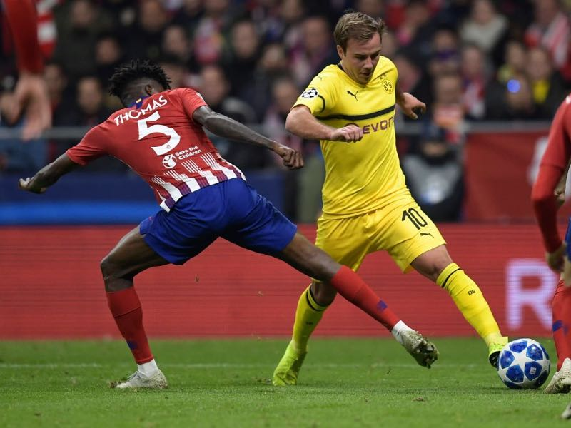 Atletico Madrid's Ghanaian midfielder Thomas (L) vies with Borussia Dortmund's German midfielder Mario Goetze during the UEFA Champions League group A football match between Club Atletico de Madrid and Borussia Dortmund at the Wanda Metropolitan stadium in Madrid on November 6, 2018. (Photo by OSCAR DEL POZO / AFP)