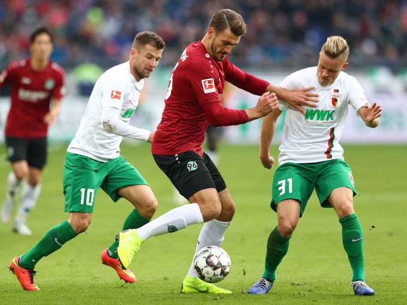 Hendrik Weydandt of Hannover 96 battles for possession with Daniel Baier and Philipp Max of Augsburg during the Bundesliga match between Hannover 96 and FC Augsburg at HDI-Arena on October 27, 2018 in Hanover, Germany. (Photo by Martin Rose/Bongarts/Getty Images)