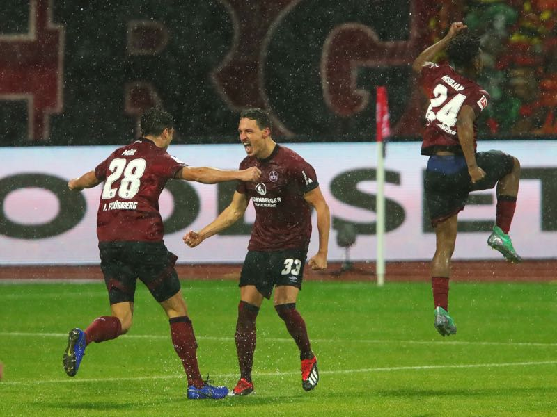 Nürnberg v Leverkusen - Georg Margreitter of Nuernberg (33) celebrates after scoring his team's first goal with Lukas Muehl (28) and Virgil Misidjan (24) during the Bundesliga match between 1. FC Nuernberg and Bayer 04 Leverkusen at Max-Morlock-Stadion on December 3, 2018 in Nuremberg, Germany. (Photo by Alexander Hassenstein/Bongarts/Getty Images)