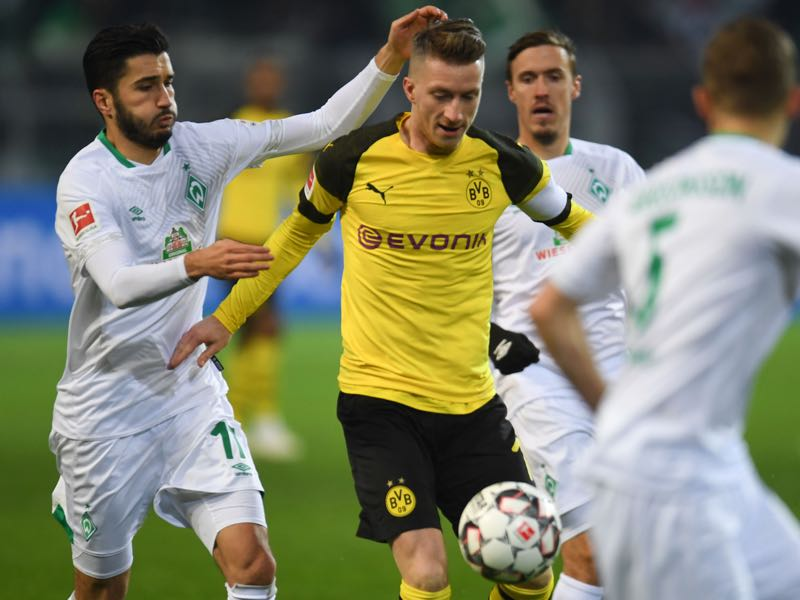 Dortmund v Bremen - Dortmund's German forward Marco Reus (C) and Bremen's Turkish forward Nuri Sahin vie for the ball during the German first division Bundesliga football match Borussia Dortmund vs Werder Bremen in Dortmund, western Germany, on December 15, 2018. (Photo by Patrik STOLLARZ / AFP)