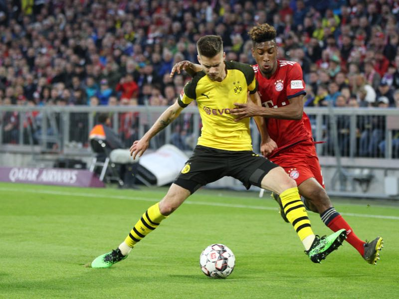Julian Weigl of Borussia Dortmund is challenged by Kingsley Coman of Bayern Munich during the Bundesliga match between FC Bayern Muenchen and Borussia Dortmund at Allianz Arena on April 06, 2019 in Munich, Germany. (Photo by Adam Pretty/Bongarts/Getty Images)