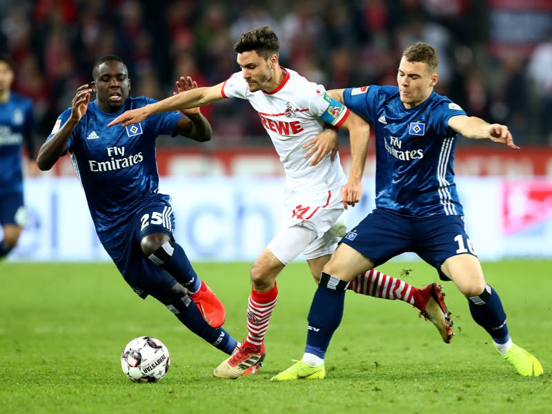 Köln v Hamburg - Jonas Hector (C) of Koeln challenge Orel Mangala and Vasilije Janjicic #16 of Hamburg during the Second Bundesliga match between 1. FC Koeln and Hamburger SV at RheinEnergieStadion on April 15, 2019 in Cologne, Germany. (Photo by Lars Baron/Bongarts/Getty Images)