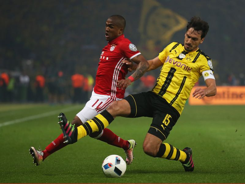 Mats Hummels of Dortmund is challenged by Douglas Costa of Bayern during the DFB Cup Final between Bayern Muenchen and Borussia Dortmund at Olympiastadion on May 21, 2016 in Berlin, Germany. (Photo by Lars Baron/Bongarts/Getty Images)